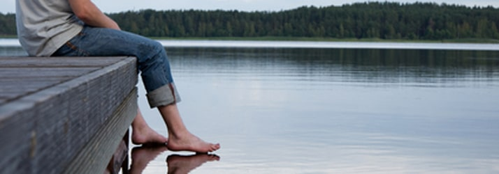 Man sitting on dock with feet touching water